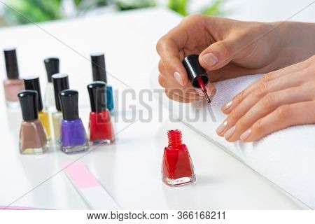 Woman Giving Herself Elegant Manicure At Home. Closeup Of Beautiful Female Hand Applying Red Nail Po