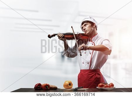 Young Male Chef With Violin Standing Near Cooking Table With Vegetables. Handsome Chef In White Hat