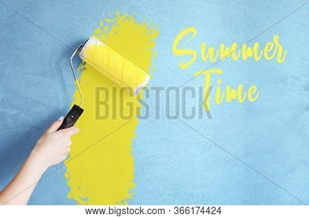 Cropped Image Of A Hand Holding A Paint Roller While Painting A House Wall In Yellow With The Inscri