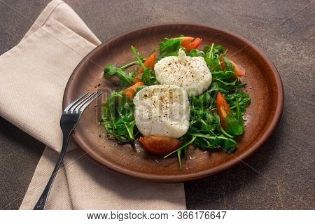 Poached Eggs On Lettuce And Arugula, On A Clay Plate. Dark Background. Healthy Breakfast