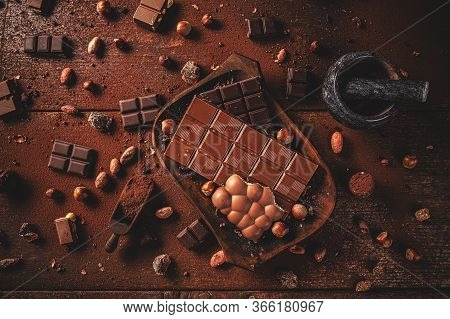 Flat Lay Of Dark Chocolate Chunks And Beans On Wooden Table