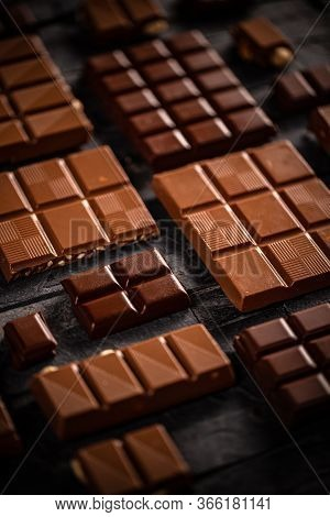 Sweet Milk And Hazelnut Chocolate Bar Pieces On Black Background