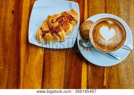 Closeup Cup Of Cappuccino In A White Cup On A Saucer With Cookies And Fresh Croissant On A Saucer. T
