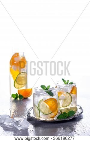 Orange Cocktail With Mint And Lime. Cold Refreshing Drink Or Beverage With Ice. Cold Drinks With Ice