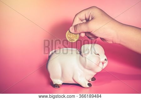 Childs Hand Drop A Coin In Piggy Bank For Saving With Pile Of Coins On Table At Home, Save Money For