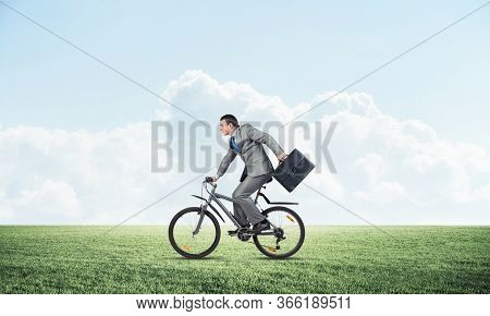 Young Man Riding Bicycle On Green Grass. Businessman On Bike Hurry To Work. Corporate Employee In Gr