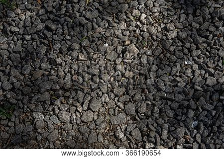 Large Compacted Rubble Lies On The Road . Dark Brown Rubble . Macadam