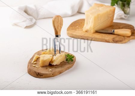 Piece Of Parmesan Cheese On  Wooden Board On White Background. Parmigiano Reggiano, Hard Mature Chee