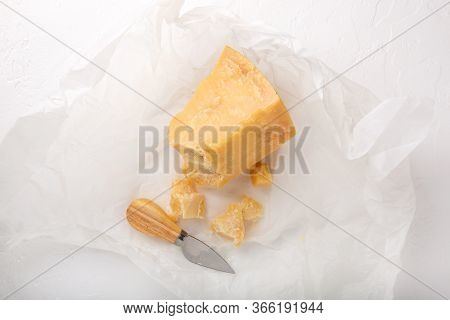 Piece Of Parmesan Cheese On White Background. Parmigiano Reggiano, Hard Mature Cheese. Top View.
