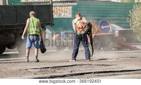A Worker Blows Off The Dust And Pours Bitumen On The Road.road Works. Workers Repair The Road Surfac