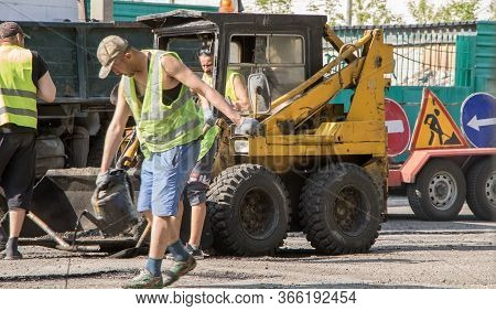 Moscow, Russia-10.05.2020: Road Works. Workers Repair The Road Surface And Asphalt The Street. Peopl
