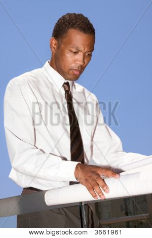 Young African American Engineer Examining Blue Print Outdoors