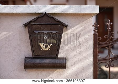 Iron Mail Box With A Magazine Stuck In It On House Wall
