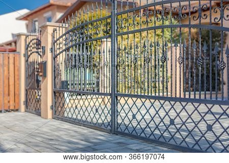 Iron Fence With Iron Gate And Blurred Luxury House Exterior. Fancy Neighborhood House And Driveway