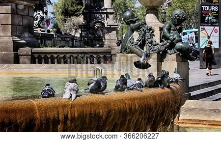 Barcelona, Catalonia, Spain - April 14, 2015: Plaça de Catalunya (Catalonia Square or Plaza de Cataluña) with water fountain, pigeons, sculptures and other artistic architecture in Barcelona.