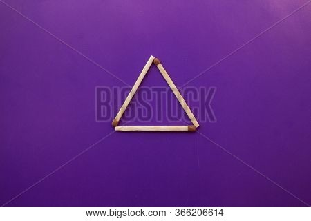 Isosceles Triangle On A Bright Background. Matchstick Pyramid On Cardboard. Education Concept