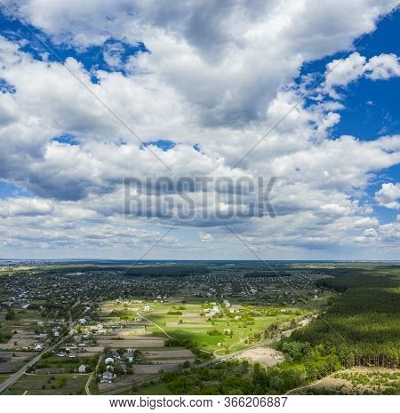 Aerial Flying Over Countryside With Village, Forest, Ponds, And Fields At Summer Time Under Dramatic