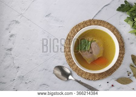 Bouillon From Homemade Chicken With Vegetables, Pepper And Bay Leaf In White Bowl On A Marble Backgr