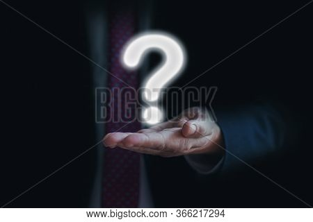 Businessman On Dark Blurred Background Holding Question Mark On His Palm. Asking For Answer Or Help