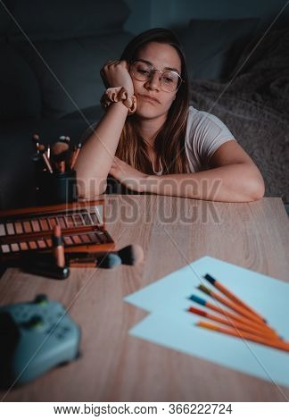 Bored Young Woman With Different Assets On A Table During Pandemic Confinement