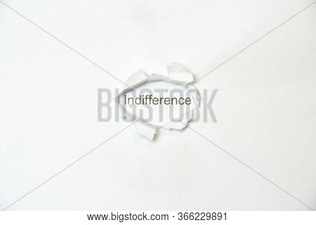 Word Indifference On White Isolated Background, The Inscription Through The Wound Hole In The Paper.