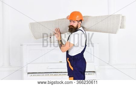 Relocating Concept. Man With Beard, Worker In Overalls And Helmet Carries Rolled Carpet, White Backg