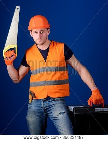Man In Helmet, Hard Hat Carries Toolbox And Holds Handsaw, Blue Background. Worker, Repairer, Repair
