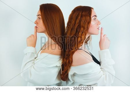 Two Redheaded Young Women Both Holding Fingers Near Lips Showing Keep Silence Sign Standing With The