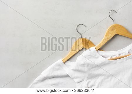 Pair Of White Pure Cotton Wrinkly T-shirts Hanging On Wooden Hangers On Gray Background. Casual Unis