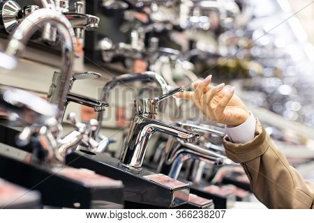Woman Is Open Faucet. Customer Hand Touches, Chooses A New Sink Faucet In The Kitchen Or Bathroom At