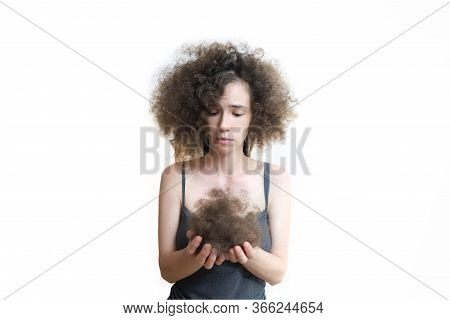 Girl Holds Her Lost Hair In Her Hands And Looks At Them With Disappointment. Fluffy Hair After Remov