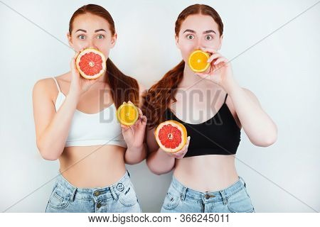 Two Redheaded Young Women Holding Two Halves Of Grapefruit And Two Halves Of Orange In Hands Standin
