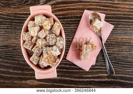 Pink Glass Bowl With Rakhat-lukum, Teaspoon And Pieces Of Rahat-lokum On Paper Napkin On Dark Wooden