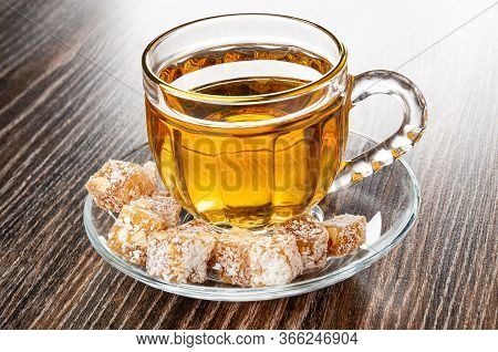 Pieces Of Rahat-lokum, Transparent Cup With Tea On Saucer On Dark Wooden Table