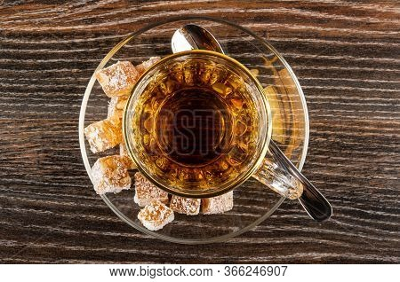 Pieces Of Rahat-lokum, Transparent Cup With Tea, Teaspoon On Saucer On Dark Wooden Table. Top View