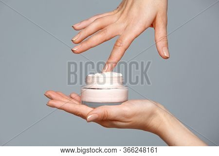 Close Up Woman Hands Holding Bottle Of White Face Cream Touching It With Finger On Blue Background.