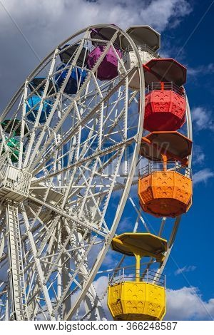 Colorful Fair Ferris Wheel On A Blue Sky With Clouds