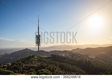 Big Telecommunications Antenna Silhouette On The Hills During Sunset With Sun Rays