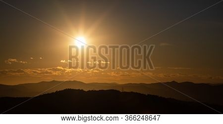 Beautiful Sunset With Sun Rays With Hills Silhouette