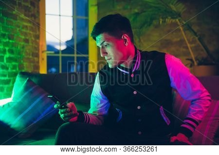 Calm. Cinematic Portrait Of Stylish Man In Neon Lighted Interior. Toned Like Cinema Effects, Bright