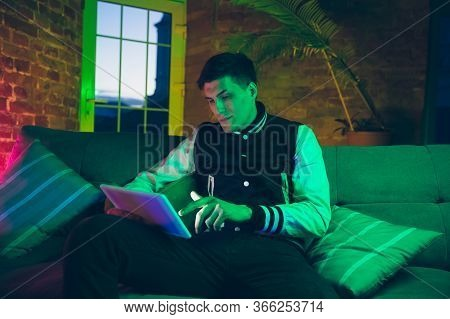 Scrolling. Cinematic Portrait Of Stylish Man In Neon Lighted Interior. Toned Like Cinema Effects, Br