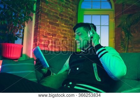 Music. Cinematic Portrait Of Stylish Man In Neon Lighted Interior. Toned Like Cinema Effects, Bright