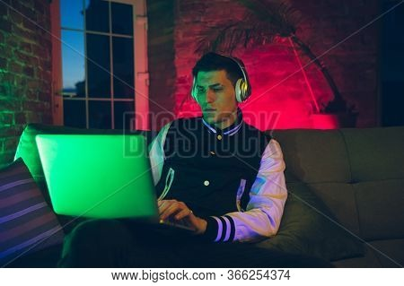Typing. Cinematic Portrait Of Stylish Man In Neon Lighted Interior. Toned Like Cinema Effects, Brigh