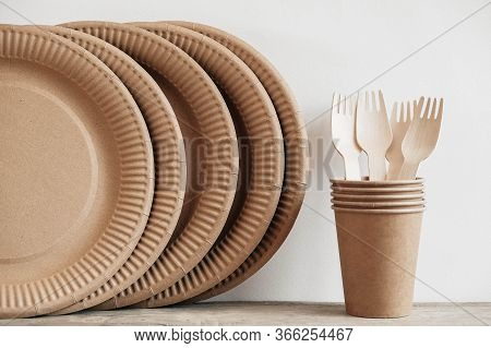 Wooden Forks And Paper Cups With Plates On Wooden Background. Eco Friendly Disposable Tableware. Als