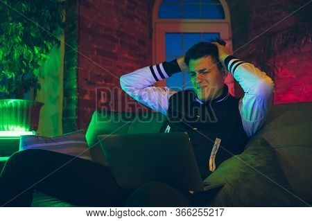 Upset. Cinematic Portrait Of Stylish Man In Neon Lighted Interior. Toned Like Cinema Effects, Bright