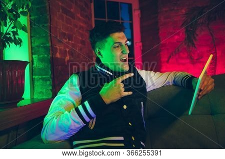Rock Sign. Cinematic Portrait Of Stylish Man In Neon Lighted Interior. Toned Like Cinema Effects, Br