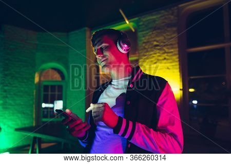 Joyful. Cinematic Portrait Of Stylish Man In Neon Lighted Interior. Toned Like Cinema Effects, Brigh