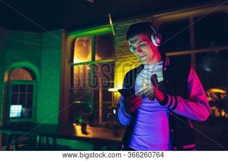Choosing Song. Cinematic Portrait Of Stylish Man In Neon Lighted Interior. Toned Like Cinema Effects
