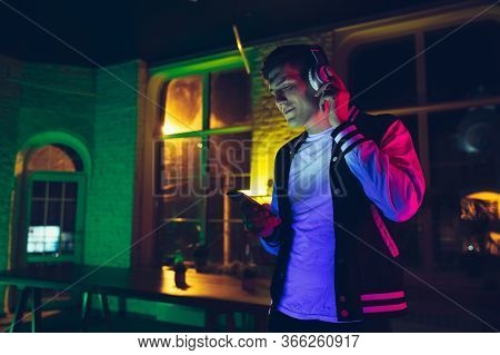 Enjoying Music. Cinematic Portrait Of Stylish Man In Neon Lighted Interior. Toned Like Cinema Effect