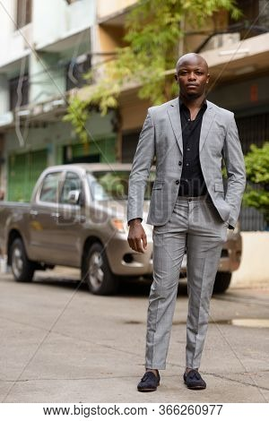 Full Body Shot Of Young Handsome Bald African Businessman In Suit Outdoors